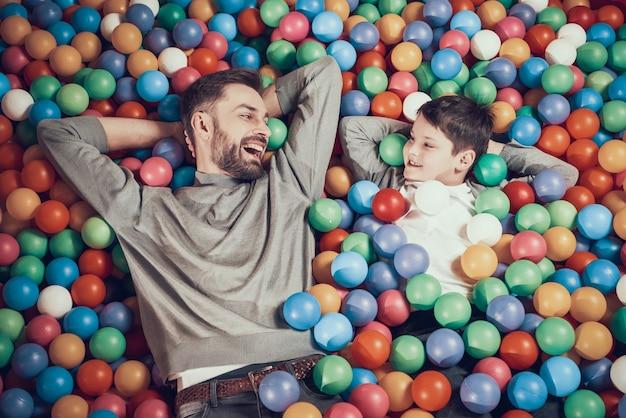 Vista do topo. joyfull pai e filho na piscina com bolas