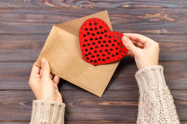 Vista do topo. mão da menina que escreve a carta de amor no dia de valentim de saint.