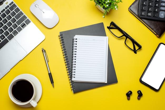 Vista do topo. mesa amarela com espaço da cópia da caneca de café do smartphone do teclado dos óculos do bloco de notas.