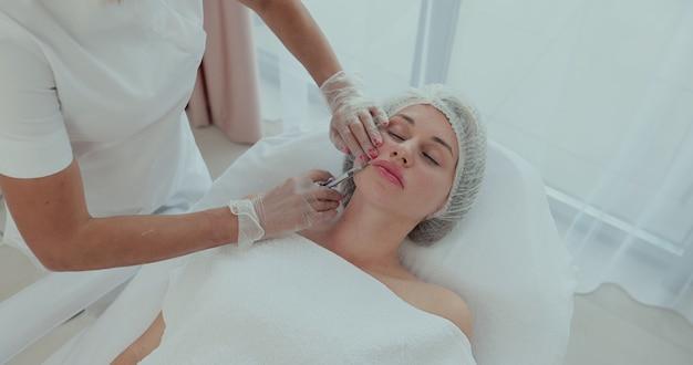 Vista do topo. mulher atraente recebe injeções anti-envelhecimento no rosto. um jovem cosmetologista experiente preenche as rugas femininas com ácido hialurônico de uma seringa.