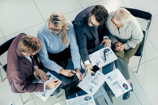 Vista do topo. o grupo de trabalho está trabalhando no relatório financeiro. conceito de negócios.