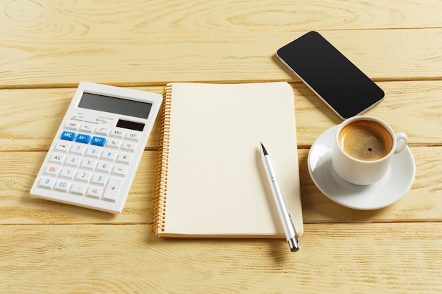 Vista do topo. xícara de café com café, smartphone, caderno em branco e calculadora na madeira