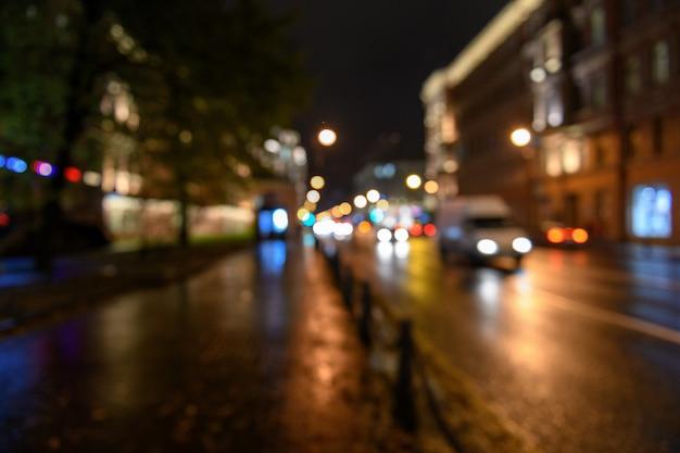 Vista do tráfego na rua da cidade turva fundo de bokeh, noite