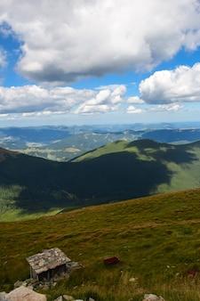 Vista do vale do topo da montanha em um fundo de montanhas verdes e céu azul com nuvens