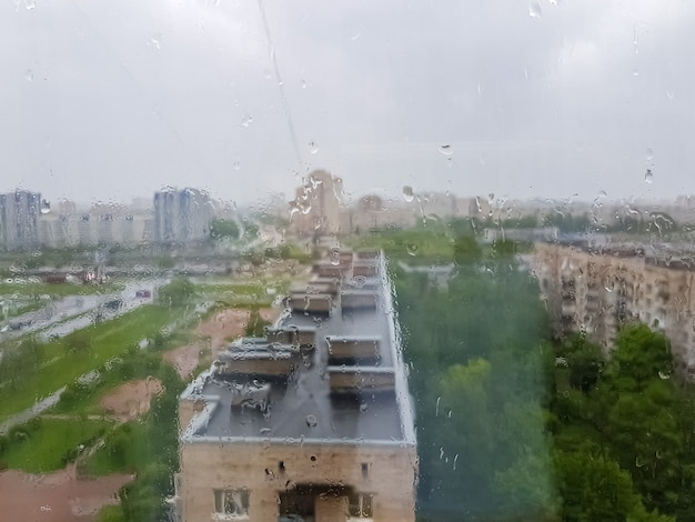 Vista do vidro da janela molhada com gotas sobre a cidade em tempo chuvoso. vista de cima