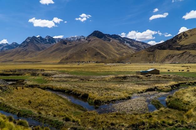 Vista dos andes, um rio e uma fazenda do expresso do oriente no peru