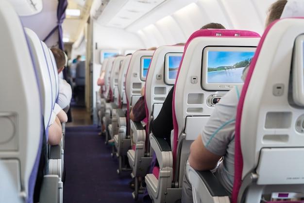 Vista dos assentos do corredor de passageiros dentro de avião