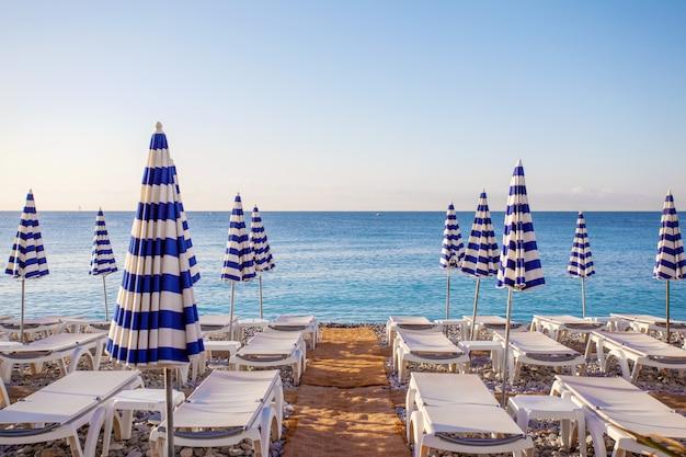Vista dos guarda-chuvas listrados azuis na praia de nice, cote d'azur, sul da frança
