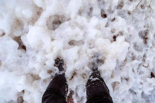Vista dos pés se afogando na espuma fria do mar espesso. mar branco.