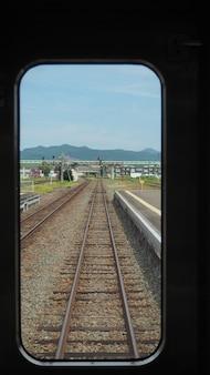 Vista dos trilhos da ferrovia de dentro do trem no japão.
