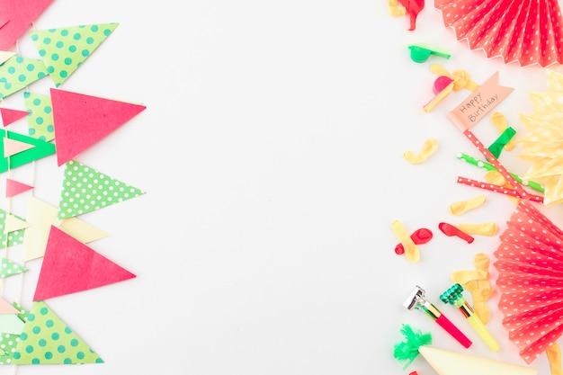 Vista elevada da bandeira de feliz aniversário; soprador de chifre de festa; balão e bunting na superfície branca