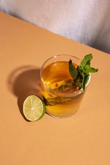 Vista elevada da bebida cocktail com limão cortados ao meio sobre a mesa marrom