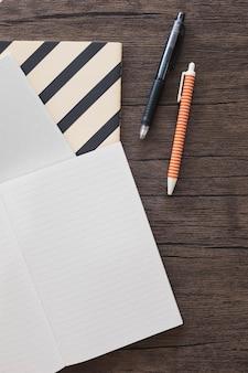 Vista elevada da caneta; caderno na mesa de madeira