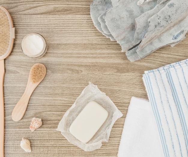 Vista elevada da esponja; concha do mar; sabonete; escova; toalha e creme hidratante em fundo de madeira
