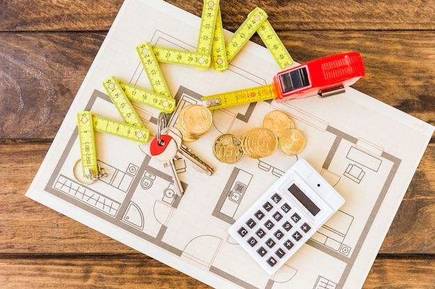 Vista elevada da fita métrica, moedas empilhadas, chave e calculadora na planta
