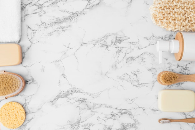 Vista elevada da luva; esponja; toalha; frasco cosmético; escova e sabão em fundo de mármore