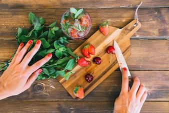 Vista elevada da mão da mulher com folha de hortelã; suco; morangos e cerejas na mesa de madeira