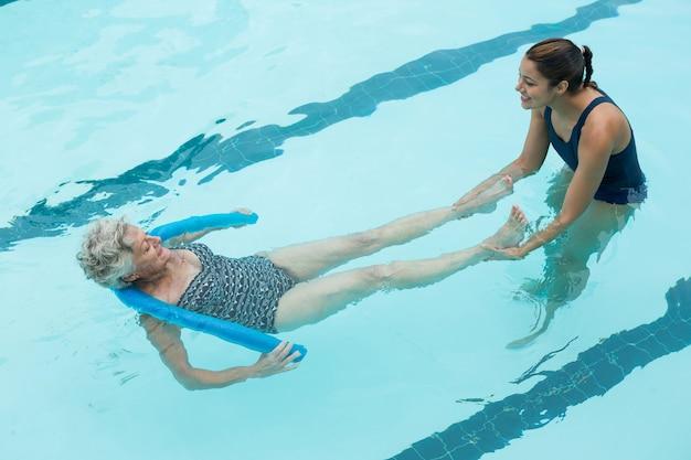 Vista elevada da treinadora sorridente ajudando idosa na piscina