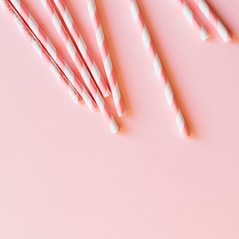 Vista elevada de bastões de doces no fundo rosa