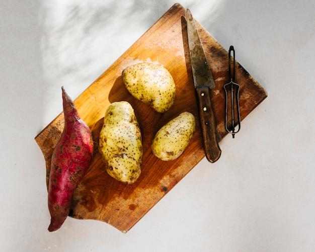 Vista elevada de batatas cruas na tábua de madeira