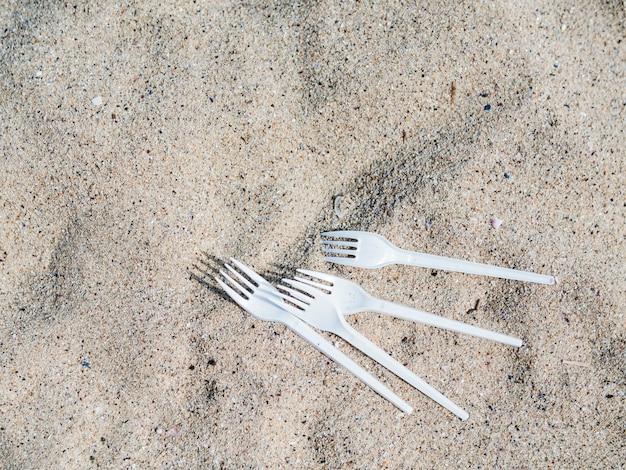 Vista elevada, de, branca, garfo plástico, ligado, areia