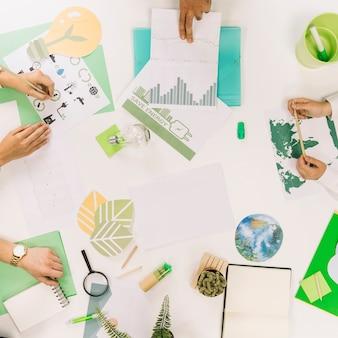 Vista elevada, de, businesspeople, mão, com, vários, recursos naturais, ícone, escrivaninha
