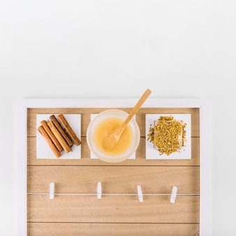 Vista elevada de canela; coalhada de limão e abelha de pólen na bandeja decorativa