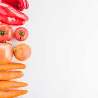 Vista elevada de cenouras; cebolas; tomates e pimentão vermelho sobre fundo branco