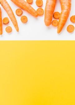 Vista elevada de cenouras em fundo branco e amarelo dual
