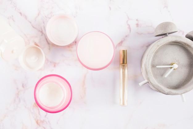 Vista elevada de cremes hidratantes; perfume e despertador em mármore