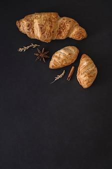 Vista elevada de croissants; especiarias e grãos em fundo preto