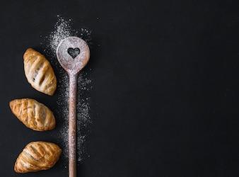 Vista elevada de croissants frescos; colher de forma de farinha e coração na superfície preta