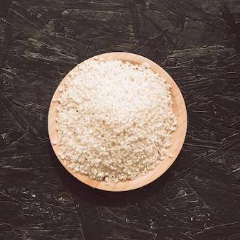 Vista elevada, de, cru, arroz, grãos, em, tigela, ligado, áspero, cinzento, fundo