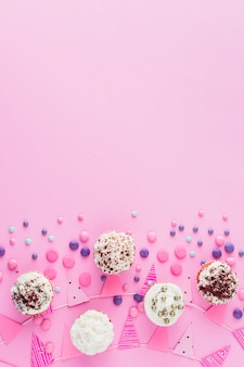 Vista elevada de cupcakes; doces e bunting na superfície rosa