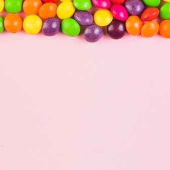 Vista elevada de doces coloridos no topo do fundo rosa