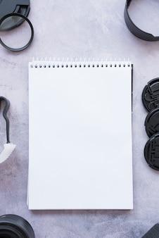 Vista elevada, de, em branco, aberta, espiral, notepad, com, câmera, acessórios, ligado, concreto, fundo