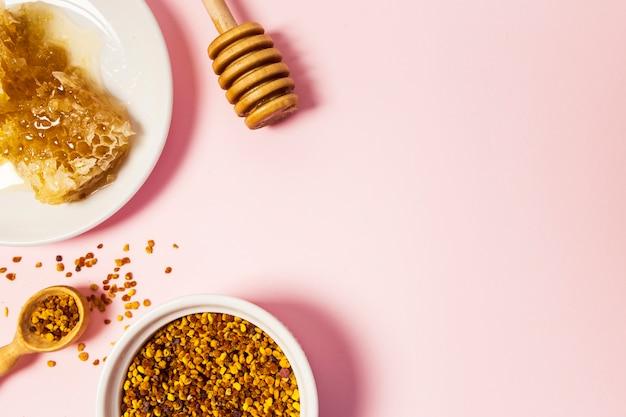 Vista elevada, de, favo de mel, e, abelha, pólen, sobre, cor-de-rosa, superfície
