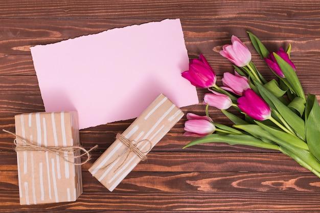 Vista elevada de flores tulipa rosa; papel rosa; e caixas de presente contra a superfície de madeira