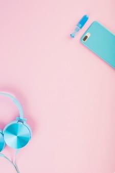 Vista elevada de fone de ouvido e smartphone em fundo rosa