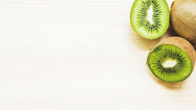 Vista elevada de frutos de kiwi cortados ao meio no fundo de madeira