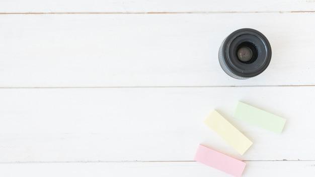 Vista elevada, de, lente câmera moderna, com, colorido, notas pegajosas, ligado, tabela madeira