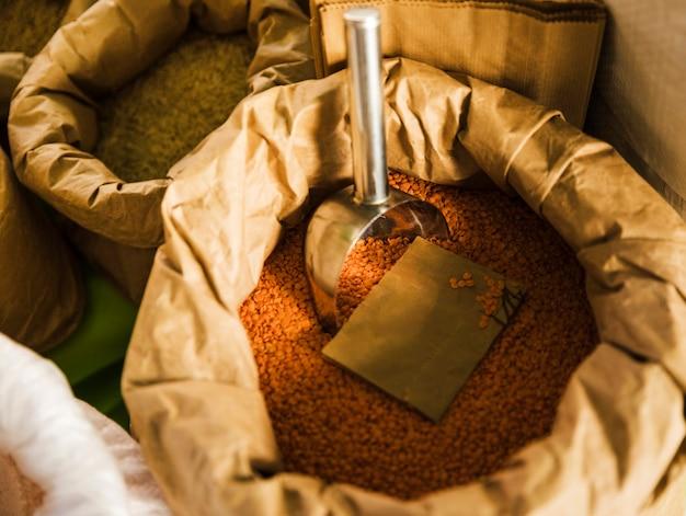 Vista elevada, de, lentilhas vermelhas, com, concha, em, sacola marrom, papel