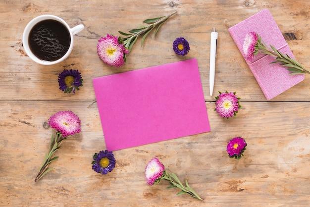 Vista elevada de lindas flores; papel rosa em branco; caneta; diário e chá preto na superfície de madeira