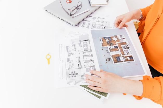 Vista elevada, de, mão feminina, segurando, blueprint, branco, escrivaninha