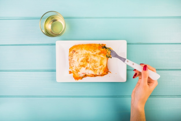 Vista elevada, de, mão mulher, comer, lasanha, ligado, prato