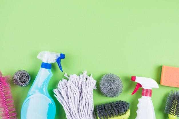 Vista elevada de material de limpeza em pano de fundo verde