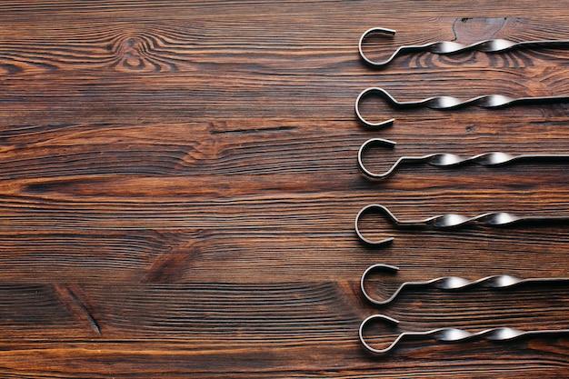 Vista elevada, de, metálico, skewer, organizado, em, fila, ligado, madeira, fundo