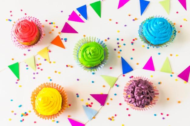 Vista elevada de muffins coloridos; bandeirinha e confete na superfície branca