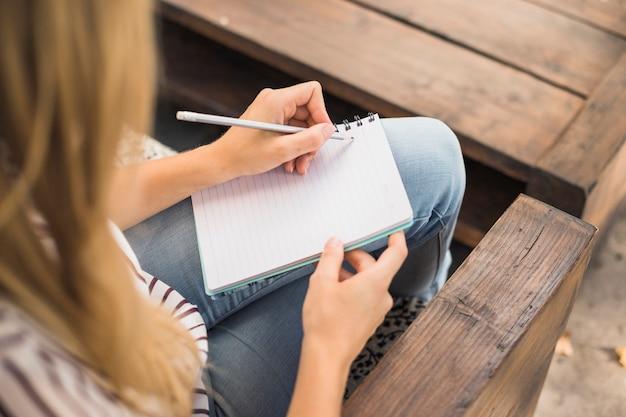 Vista elevada, de, mulher, escrita, ligado, caderno