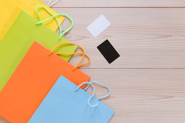 Vista elevada de multi coloridas sacolas com cartão em branco na mesa de madeira